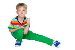 Mody chłopiec siedzi jego kciuk up i trzyma obrazy royalty free