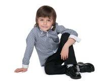 Mody chłopiec siedzi na podłoga obraz stock