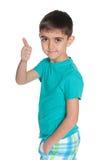 Mody chłopiec trzyma jego kciuk up zdjęcie stock