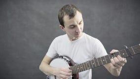 Młody człowiek bawić się bandżo Czarny tło zbiory wideo