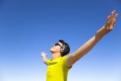 Młody człowiek cieszy się muzykę z niebieskiego nieba tłem Zdjęcie Royalty Free