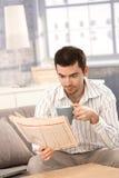 Młody człowiek czytelniczej wiadomości pije herbata w ranku Zdjęcia Stock
