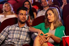 Młody człowiek molestuje dziewczyny w kinie na pierwszy dacie Obraz Stock