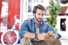 Młody człowiek opowiada telefon komórkowego w ulicie Obrazy Royalty Free