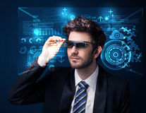 Młody człowiek patrzeje z futurystycznymi mądrze zaawansowany technicznie szkłami Fotografia Stock