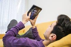 Młody człowiek siedzi indoors brać selfie lub wideo Fotografia Royalty Free