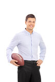 Młody człowiek trzyma futbol amerykańskiego Fotografia Royalty Free