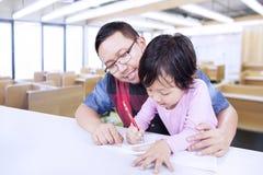 Młody człowiek uczy małej dziewczynki pisać Obraz Stock