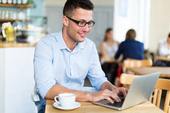 Młody człowiek używa laptop przy kawiarnią Obrazy Royalty Free