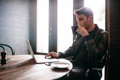 Młody człowiek używa laptop przy kawiarnią Zdjęcie Royalty Free