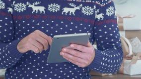 Młody człowiek w dzianina pulowerze z deers używać pastylkę zdjęcie wideo