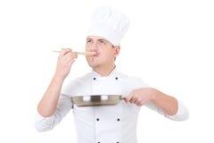 Młody człowiek w szefa kuchni munduru degustaci coś odizolowywający na bielu Fotografia Stock