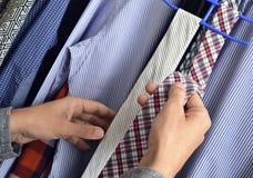 Młody człowiek wybiera krawat od szafy Zdjęcia Royalty Free