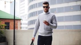 Młody człowiek z okularami przeciwsłonecznymi i torby odprowadzenie w mieście zdjęcie wideo