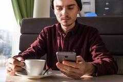 Młody człowiek z smartphone ma kawę przy kawiarnią Obrazy Stock