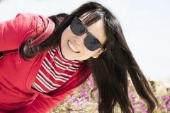 Mody dziewczyna ono uśmiecha się będący ubranym okulary przeciwsłoneczni obrazy royalty free