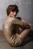 Mody dziewczyna w złoto sukni obsiadaniu na podłoga przy studiiem zdjęcie stock