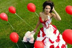 Mody dziewczyna z baloons na trawy bacground Obraz Royalty Free