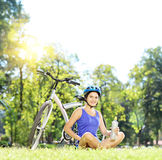 Młody żeński rowerzysty obsiadanie na trawie obok drinkin i roweru Fotografia Stock