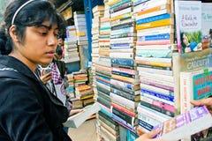 Młody żeński uczeń wybiera książkę na rynku Fotografia Stock
