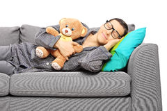 Młody faceta dosypianie na kanapie trzyma misia Zdjęcie Stock
