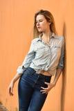Mody fotografia pozuje na pomarańcze ściany tle ładna młoda kobieta Obraz Stock