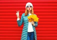 Mody jesieni kobieta trzyma żółtych liście klonowych, dmucha czerwone wargi fotografia stock