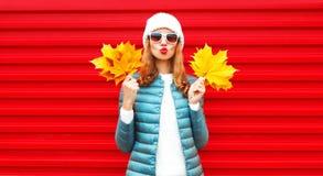 Mody jesieni portreta kobieta trzyma żółtych liście klonowych obraz stock