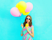 Mody kobiety ładnych napojów owocowy sok od filiżanki trzyma lotniczych kolorowych balony Obraz Royalty Free