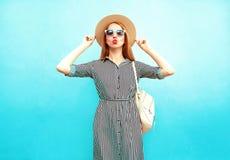 Mody kobiety pozy w pasiastej sukni i round słomianym kapeluszu zdjęcie royalty free