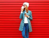 Mody młoda kobieta pije kawowego używa smartphone na czerwonym tle obraz royalty free