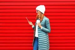 Mody młoda kobieta używa smartphone z filiżanką zdjęcia royalty free