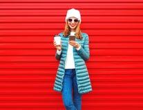 Mody młoda kobieta używa smartphone z filiżanką na czerwieni obraz stock