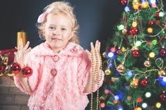 Mody mała dziewczynka dekoruje choinki Zdjęcia Royalty Free