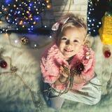 Mody mała dziewczynka dekoruje choinki Zdjęcie Royalty Free