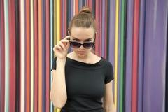 Mody miastowy stylowy pojęcie Damy twarzy tajemniczy zrywanie z czarnych eyeglasses przed pasiastą kolorową ścianą wewnątrz fotografia stock