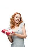 Młody miedzianowłosy szczęśliwy uśmiechnięty dziewczyny mienia prezent Obrazy Royalty Free