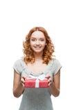 Młody miedzianowłosy szczęśliwy uśmiechnięty dziewczyny mienia prezent Fotografia Stock