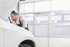 Młody męski utrzymanie inżynier naprawia samochodowego silnika w warsztacie Fotografia Royalty Free
