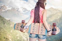 Mody nastoletnia dziewczyna z longboard deskorolka przy górą Zdjęcia Royalty Free
