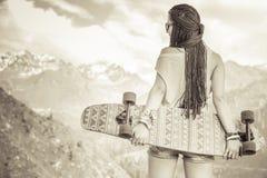 Mody nastoletnia dziewczyna z longboard deskorolka przy górą Obraz Royalty Free