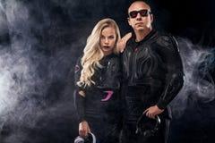 Mody pary model DJ i rowerzysta z hełmofonami i okularami przeciwsłonecznymi, czarna skórzana kurtka, rzemienni spodnia, eleganck zdjęcie royalty free