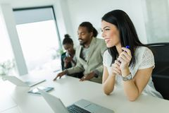 Młody piękny bizneswomanu obsiadanie przy biurowym biurkiem z col Fotografia Royalty Free