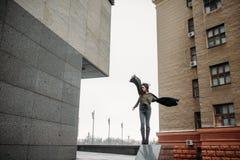 Mody pojęcie: piękna młoda dziewczyna z długie włosy, szkłami, czerwonymi wargami i popielatym je, stoi blisko nowożytnej ściany  Zdjęcia Royalty Free