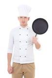 Młody przystojny mężczyzna szef kuchni smaży niecki isolat w mundurze z teflon Zdjęcia Stock