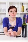 Młoda smutna thinkful kobieta pije szkło czerwone wino Zdjęcia Royalty Free