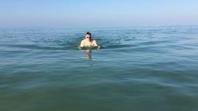 Młody sportowy mężczyzna pływa w morzu zdjęcie wideo
