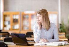 Młody studencki używa komputer w bibliotece patrząc z Obrazy Royalty Free
