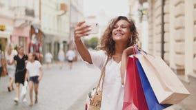 Mody szczęśliwa dosyć chłodno młoda kobieta z torba na zakupy robi fotografia autoportretowi na smartphone zdjęcie wideo