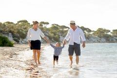Młody szczęśliwy matki i ojca odprowadzenie z małą córką na plaży w rodzinnego wakacje pojęciu Zdjęcia Royalty Free